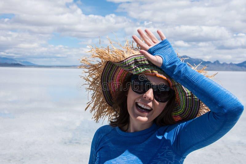 Den vuxna kvinnlign som bär den fåniga sugrörhatten och solglasögon, skyddar henne ögon från solen arkivbild