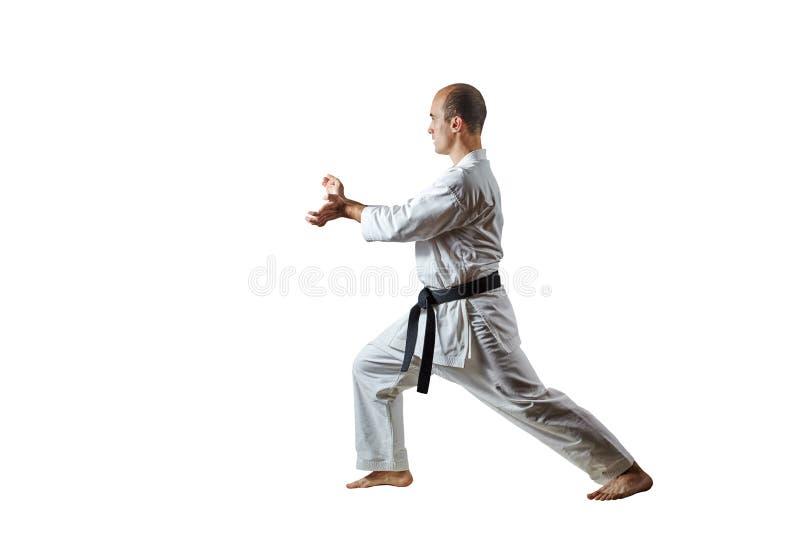 Den vuxna manliga idrottsman nen utför formella karateövningar på en vit isolerad bakgrund arkivbild
