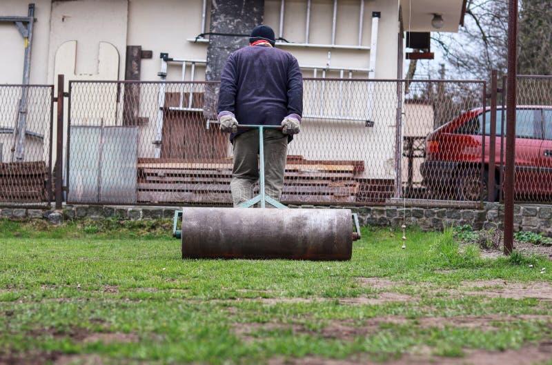 Den vuxna mannen gör trädgården slätare med hjälpgräsmattarullen Smutsigt och hårt arbete i trädgården Sommarvolontären drar den  royaltyfri bild
