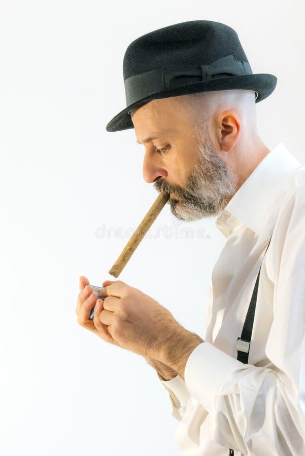 Den vuxna mannen röker cigarren med hatten royaltyfri bild