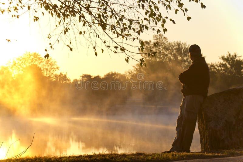 Den vuxna mannen står bara på soluppgång som stirrar in mot den dimmiga sjön