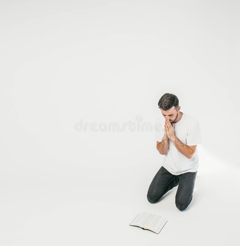 Den vuxna mannen står på hans knä och ber, medan hans ögon ser ner till golvet Där är en bibel i arkivfoto
