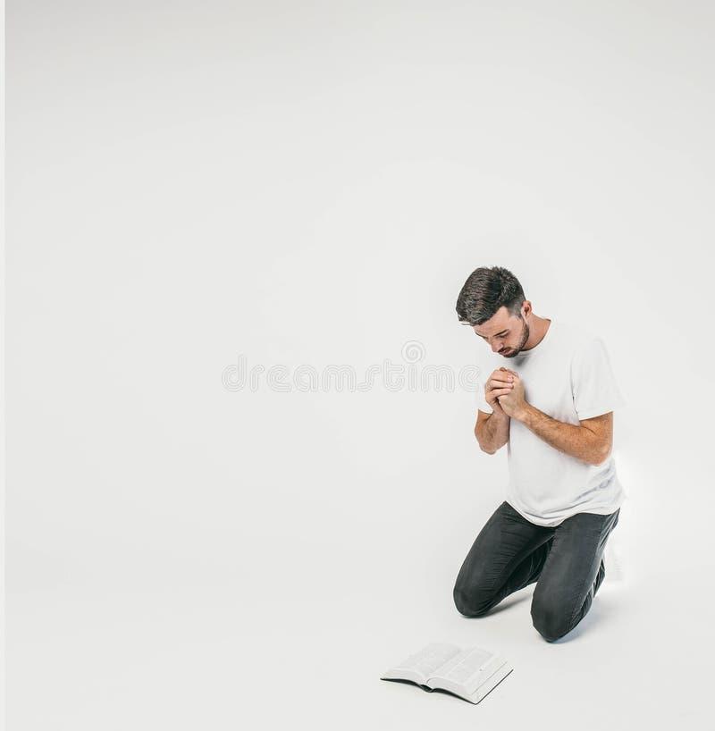 Den vuxna mannen står på hans knä och ber, medan hans ögon ser ner till golvet Där är en bibel i arkivbilder