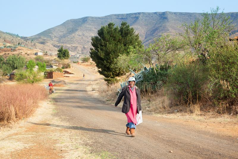 Den vuxna roliga le afrikanska kvinnan i ljus klänning på den autentiska bygatan, den gamla lyckliga skratta basothokvinnan går p fotografering för bildbyråer