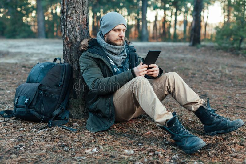 Den vuxna stiliga manliga handelsresanden sitter på höstpinjeskog nära trädet som rymmer på minnestavlarekreation som vilar loppd arkivfoton