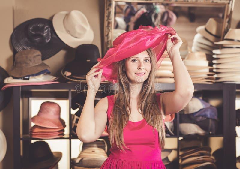 Den vuxna trevliga kvinnan försöker på den rosa platt halmhatthatten i shoppinggalleria royaltyfria bilder