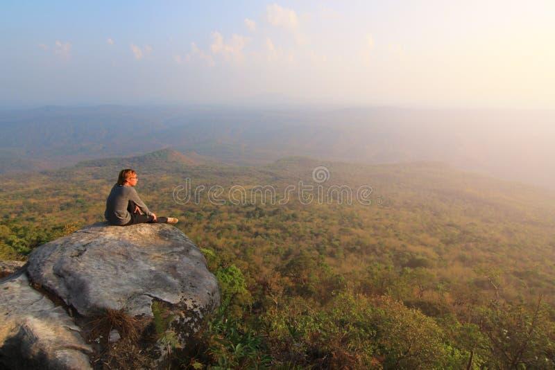 Den vuxna turisten i svart byxa, omslaget och mörkerlocket sitter på klippans kant och att se dimmig bergig dalbröl arkivfoto