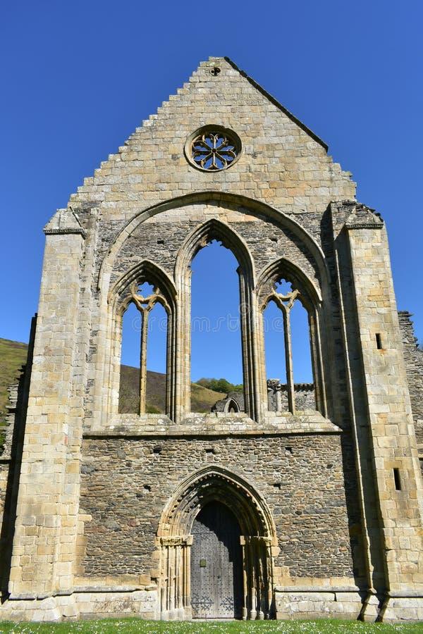 Den Wales Valle Crucis abbotskloster, en ljust tänd sol för vägg på våren royaltyfri bild
