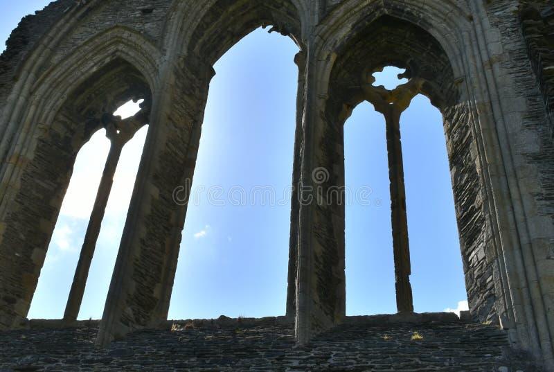 Den Wales Valle Crucis abbotskloster, ett sillouetted fönster arkivbilder