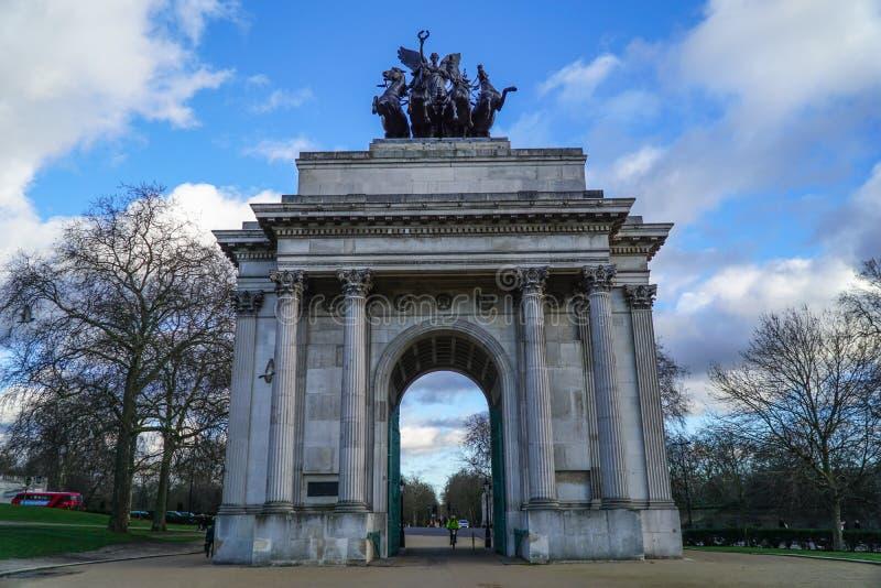 Den Wellington Arch eller konstitutionbågen är en triumf- båge som lokaliseras till söderna av Hyde Park i London Dramatiskt moln royaltyfria bilder