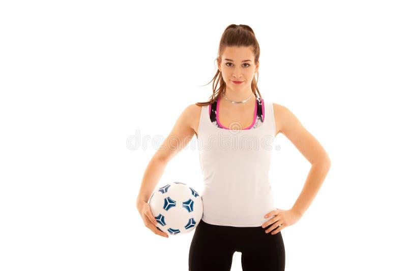 Den Woamn fotbollspelaren rymmer en boll isolerad över vit bakgrund arkivfoto