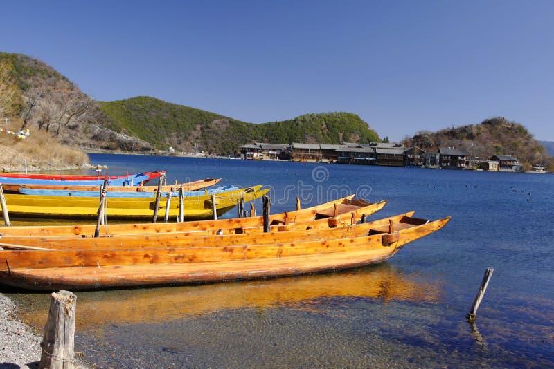 Den Wood fiskebåten som svävar på Lugu för blått vatten som den sceniska fläcken för sjön omges av snöberget, och högt himmelmörk royaltyfri foto