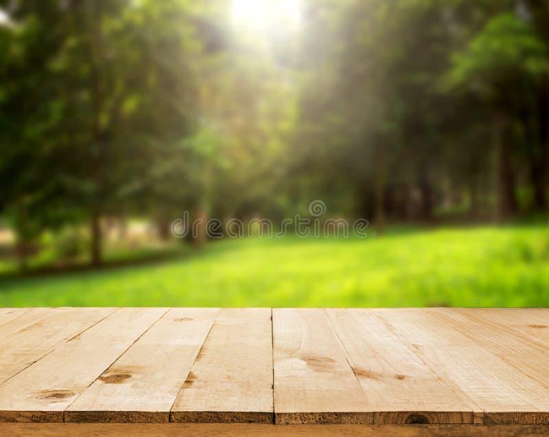 Den Wood tabellöverkanten på skinande solljusbokehbakgrund - kunna använt för royaltyfria foton