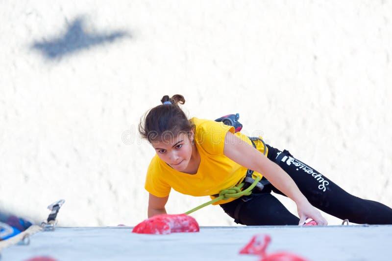 Den yngre kvinnliga idrottsman nen gör hård flyttning på klättringväggen arkivbild