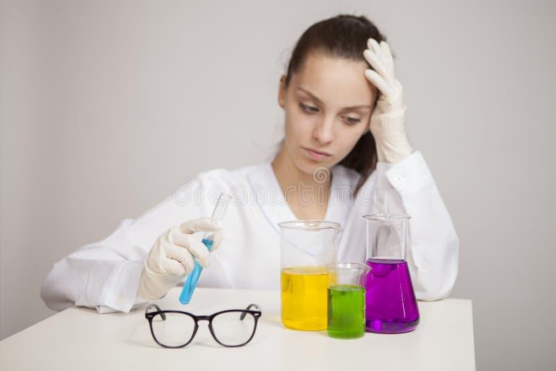 Den Yong kvinnan gör det kemiska provet i laboratorium royaltyfria bilder