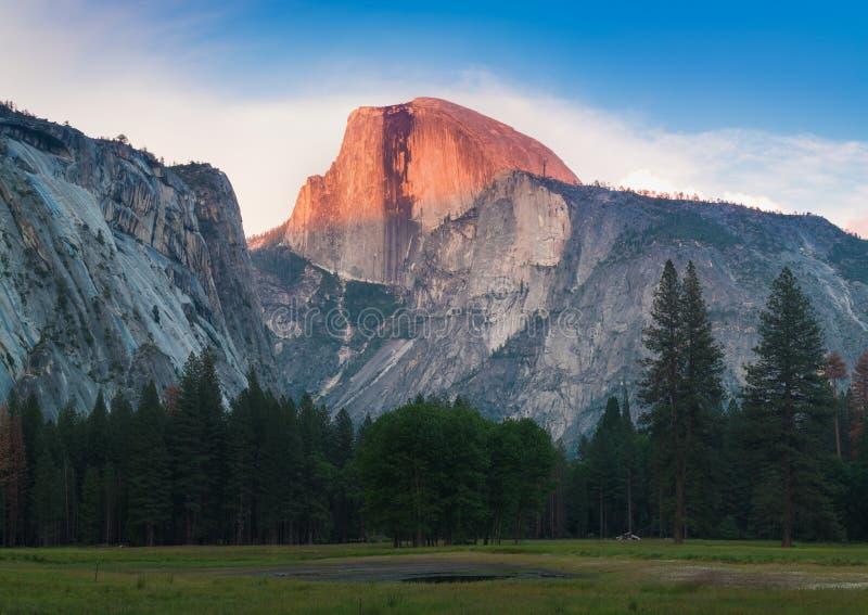 Den Yosemite nationalparksikten av den halva kupolen från dalen under färgrik solnedgång med träd och vaggar Kalifornien USA arkivfoton