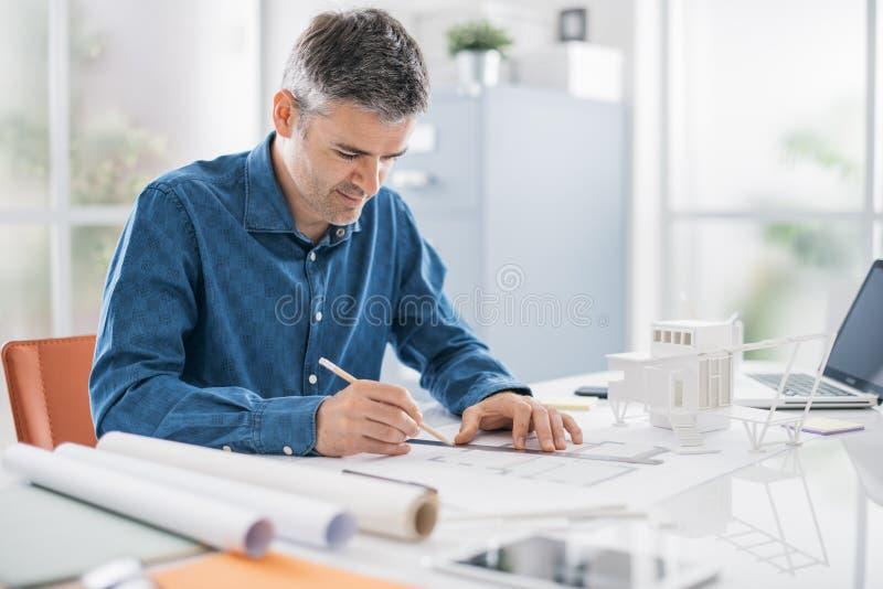 Den yrkesmässiga arkitekten som arbetar på kontorsskrivbordet, är han dra och göra mätningar på en projektritning, teknik och royaltyfri bild