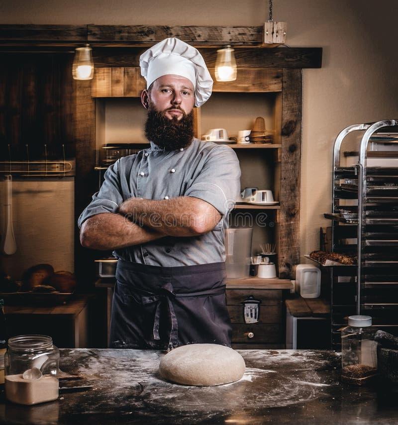 Den yrkesmässiga bagaren i kocklikformign som poserar med korsade armar nära, bordlägger med klar deg i bagerit arkivfoton