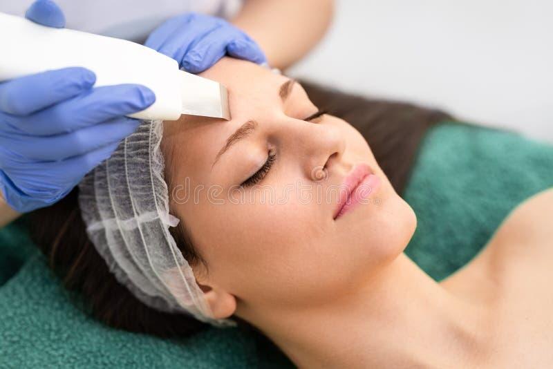 Den yrkesmässiga cosmetologisten genomgår ansikts- behandling för cavitation arkivfoto