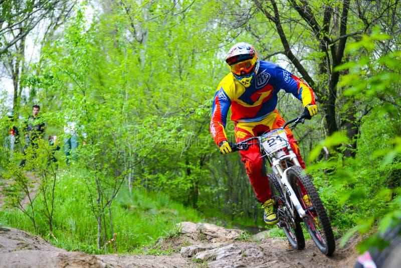 Den yrkesmässiga DH-cyklisten rider en mountainbike på slingan av den Khortytsya ön under järnbrokonkurrensen, en etapp av D royaltyfria bilder