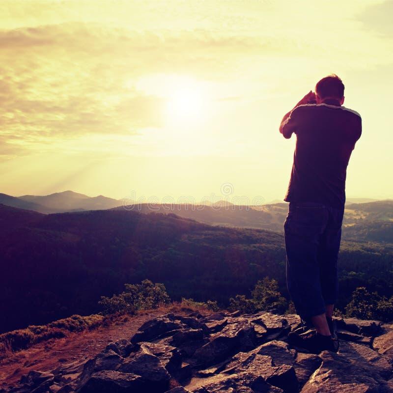 Den yrkesmässiga fotografen i jeans och skjorta tar foto med spegelkameran på maximum av vaggar Drömlikt landskap, orange sol på  arkivbild