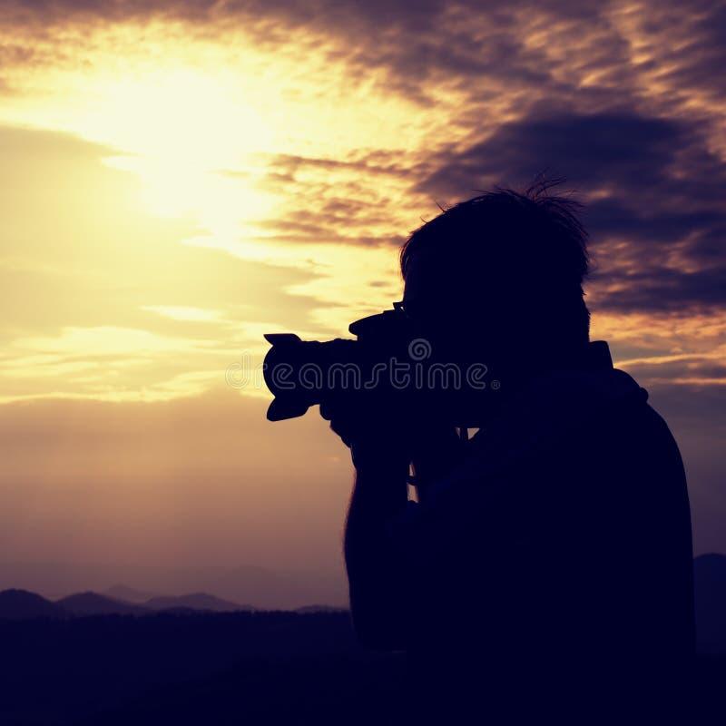 Den yrkesmässiga fotografen i jeans och skjorta tar foto med spegelkameran på maximum av vaggar Drömlikt landskap, orange sol på  royaltyfria foton