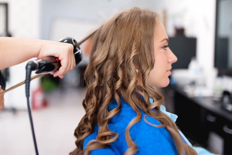 Den yrkesmässiga frisören som använder krullande järn för hår, krullar arkivbild