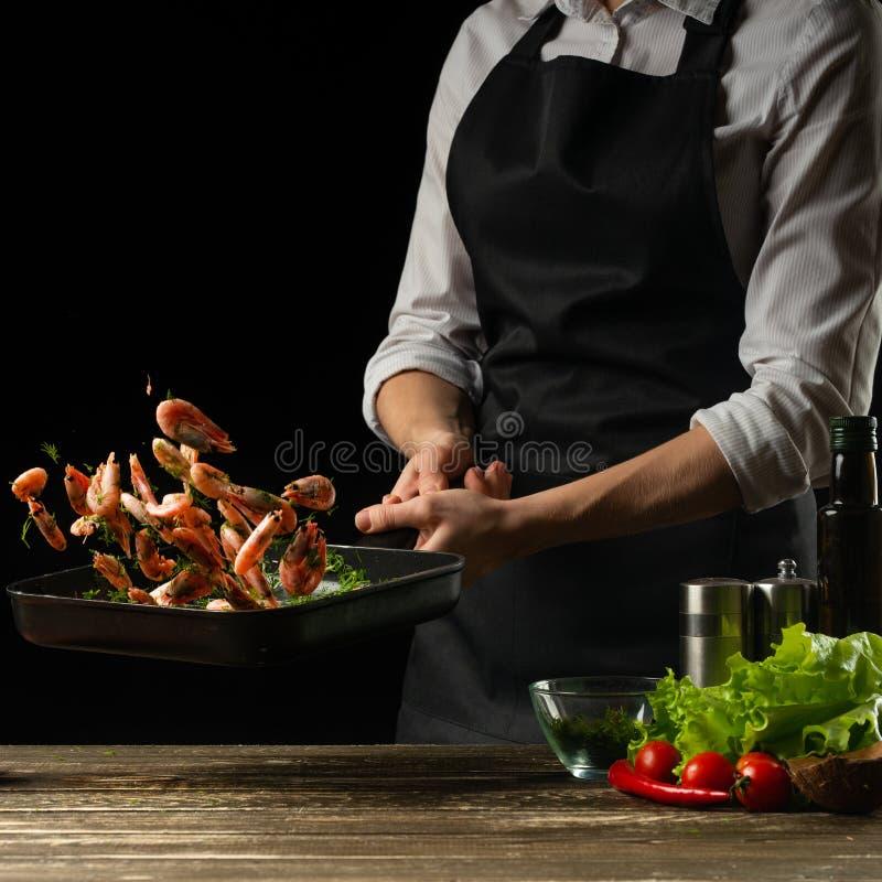 Den yrkesmässiga kocken förbereder en sallad av ny räka och grönsaker på en mörk bakgrund som fryser i rörelse Havs- och sunt arkivfoton