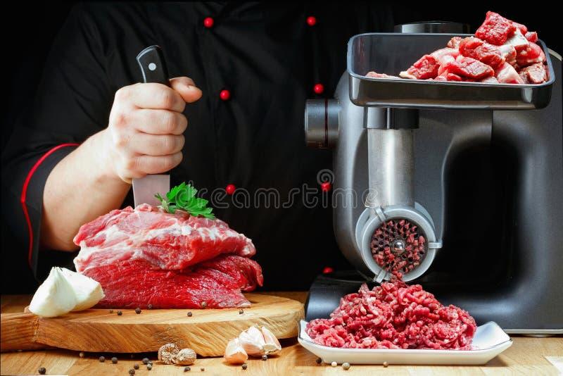 Den yrkesmässiga kocken förbereder köttfärs från nytt kött på mörk bakgrund arkivbild
