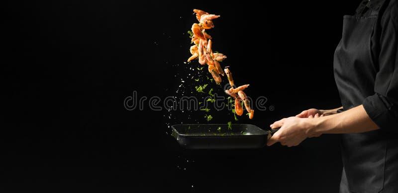 Den yrkesmässiga kocken förbereder räkor med gräsplaner Laga mat havs- sund vegetarisk mat och mat på en mörk bakgrund horizonta arkivfoto