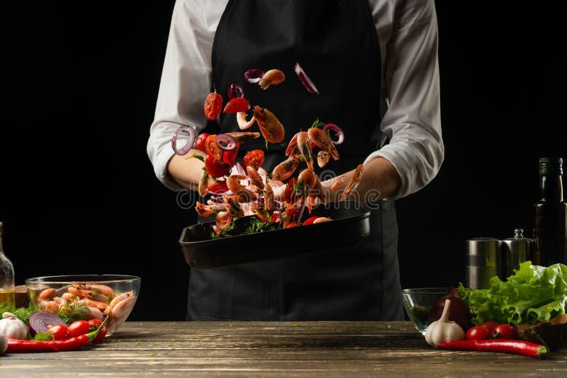 Den yrkesmässiga kocken kastade räkor med grönsaker på gallerpannan som fryser i rörelse, begrepp av havs- och sund mat royaltyfria foton