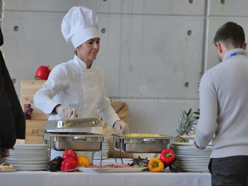 Den yrkesmässiga kvinnliga kocken förbereder buffémat för kunder royaltyfri fotografi