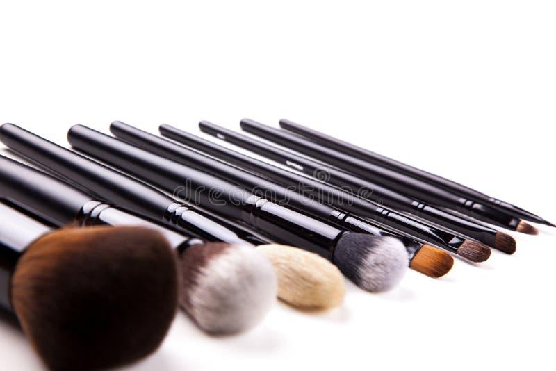 Den yrkesmässiga makeupborsten, olika sminkborstar är på vit bakgrund sorterat i linjen royaltyfria bilder