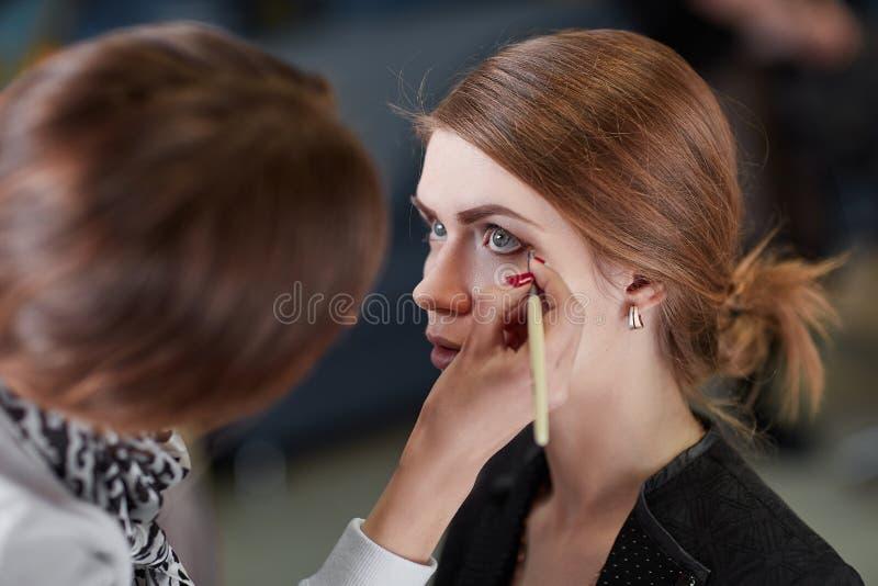 Den yrkesmässiga makeupkonstnären gör makeup för en ung kvinna fotografering för bildbyråer