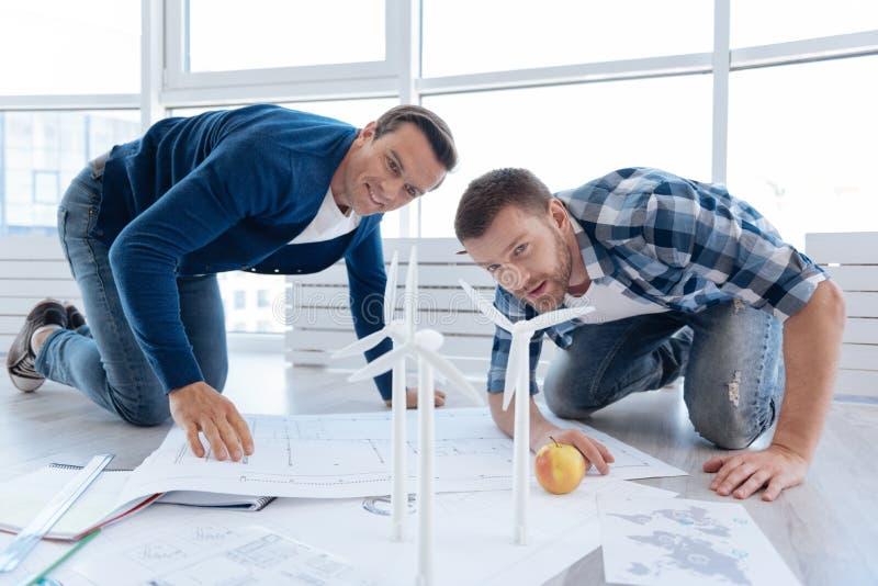 Den yrkesmässiga mannen iscensätter att se väderkvarnmodellerna fotografering för bildbyråer