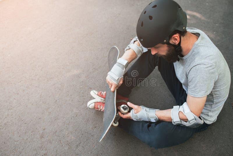 Den yrkesmässiga skateboradåkaren kontrollerar hans skateboard arkivbilder