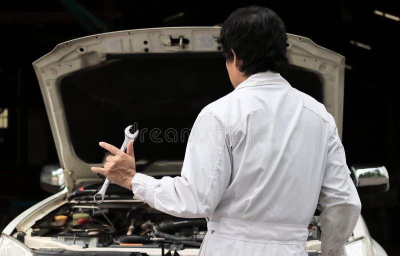 Den yrkesmässiga skiftnyckeln för mekanikermaninnehavet och hans hand med älskar jag dig tecknet med bilen i öppen huv på reparat royaltyfria bilder