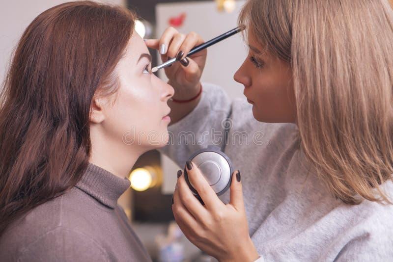 Den yrkesmässiga sminkkonstnären applicerar mascara till en ung caucasian w arkivfoto
