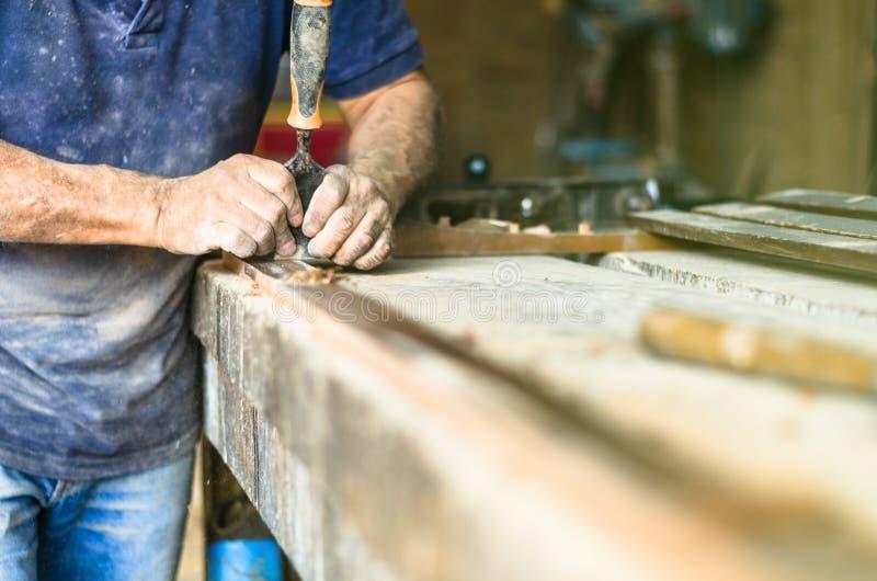 Den yrkesmässiga snickaren på arbete, snider han trä genom att använda ett snickerihjälpmedel, händer stänger sig upp, snickeri o royaltyfri foto