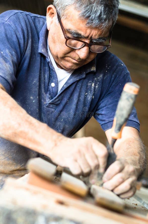 Den yrkesmässiga snickaren på arbete, snider han trä genom att använda ett snickerihjälpmedel, händer stänger sig upp, snickeri o royaltyfri bild