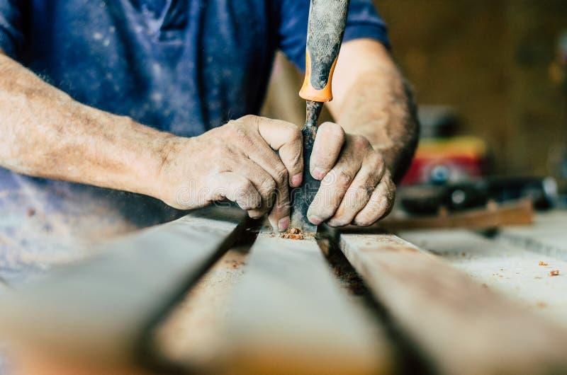 Den yrkesmässiga snickaren på arbete, snider han trä genom att använda ett snickerihjälpmedel, händer stänger sig upp, snickeri o arkivbild