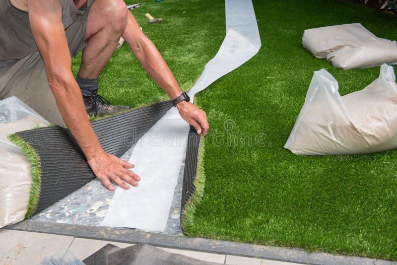 Den yrkesmässiga trädgårdsmästaren är bitande konstgjord torva som ska passas arkivbild
