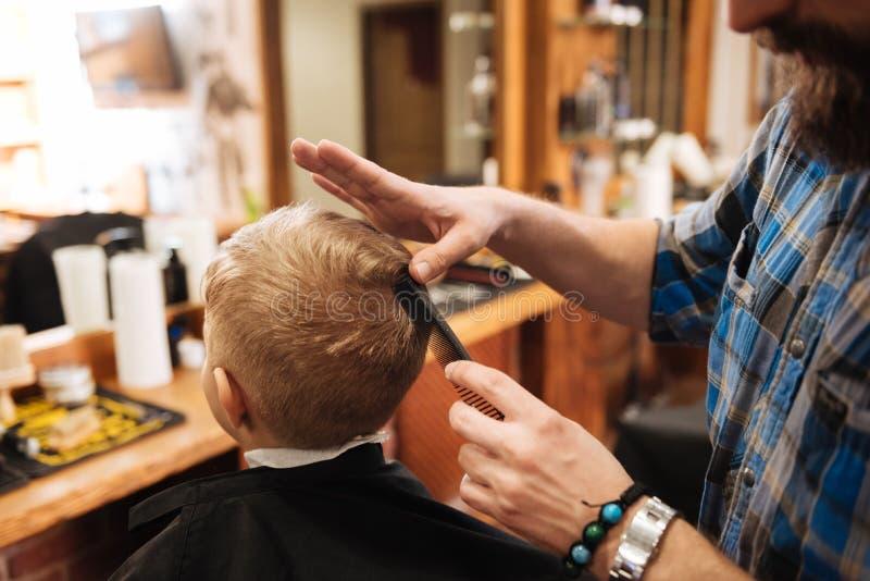 Den yrkesmässiga trevliga barberaren som trycker på överkanten av pojkarna, head arkivfoto