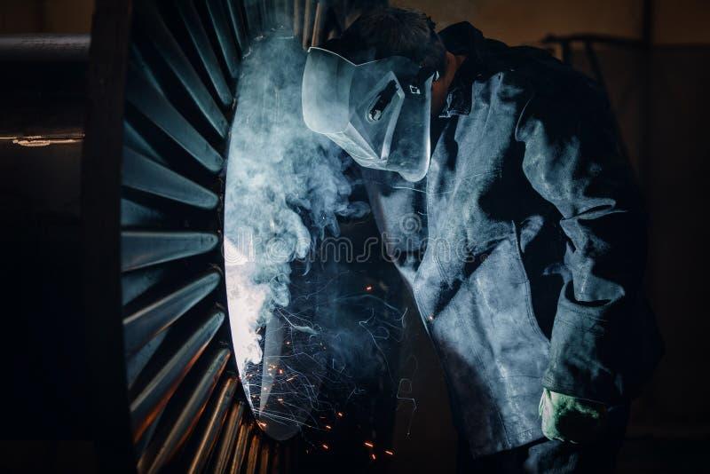 Den yrkesmässiga welderen utför svetsande arbete på metall i skyddande maskering Industriarbetarebegrepp royaltyfri foto