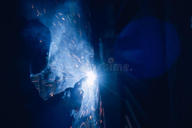 Den yrkesmässiga welderen utför svetsande arbete på metall i skyddande maskering Industriarbetarebegrepp arkivbild