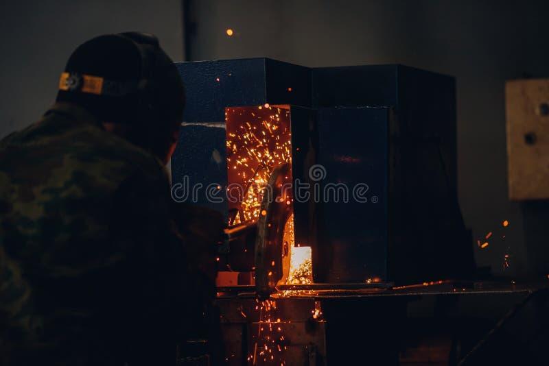 Den yrkesmässiga welderen utför svetsande arbete på metall i skyddande maskering Industriarbetarebegrepp royaltyfri fotografi