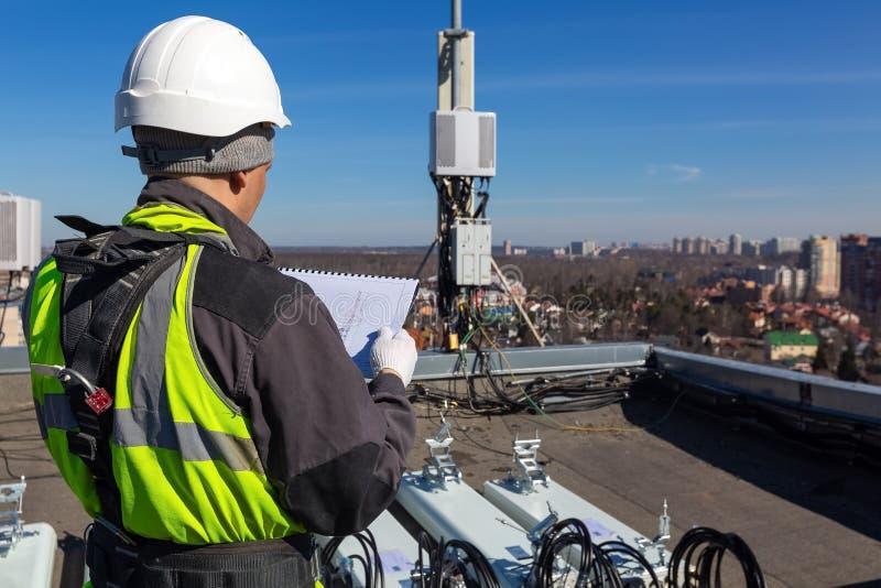 Den yrkesm?ssiga industriella kl?ttraren i hj?lm och likformig l?ser tekniska dokumentation och antenner av g-/m2DCS UMTS LTE arkivbild
