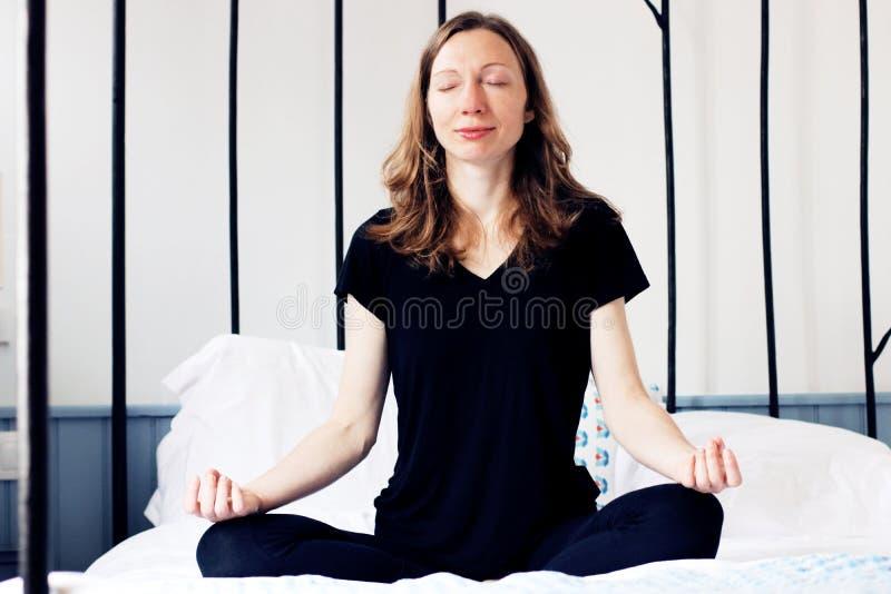 Den Zen Business kvinnan som gör yogameditation på säng, kopplade av i lotusblomma poserar arkivfoton