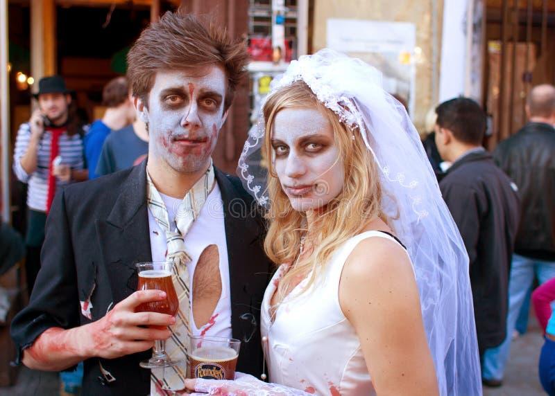 Den Zombiebruden och brudgummen tycker om en kall öl royaltyfri fotografi