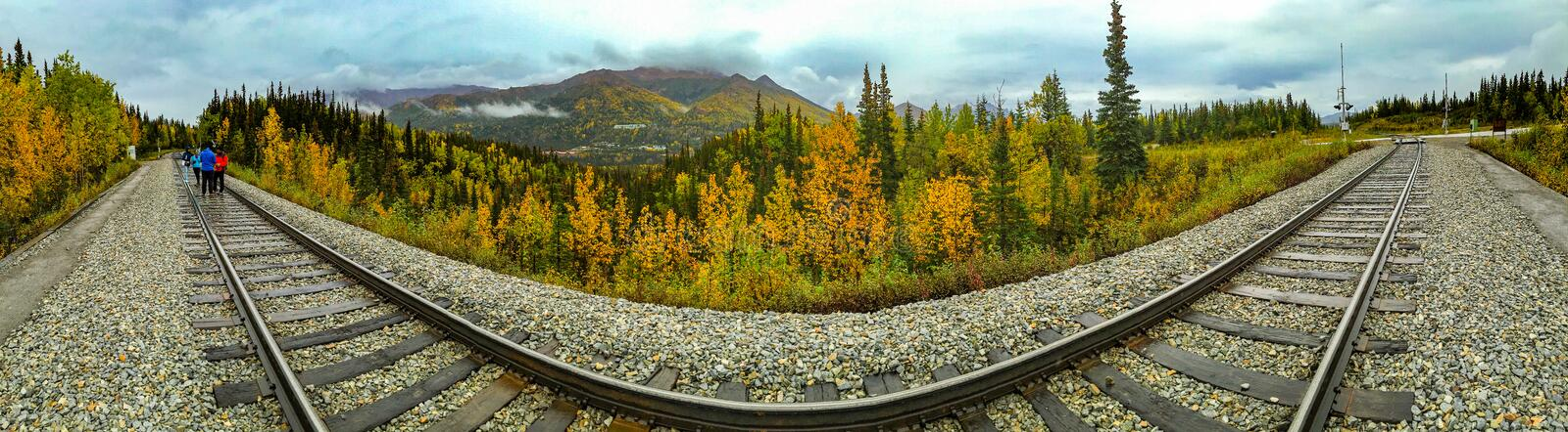 Denali Train Tracks. Denali, Alaska, USA - Sept. 5, 2016: Distorted perspective panorama of railroad tracks skirting through Denali National Park. Tracks are stock image